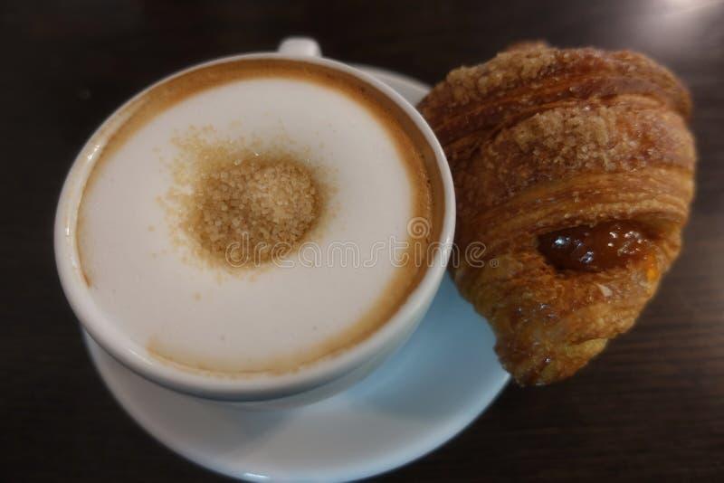 Café da manhã italiano com um cappuccino, açúcar mascavado e um croissant fresco imagem de stock royalty free