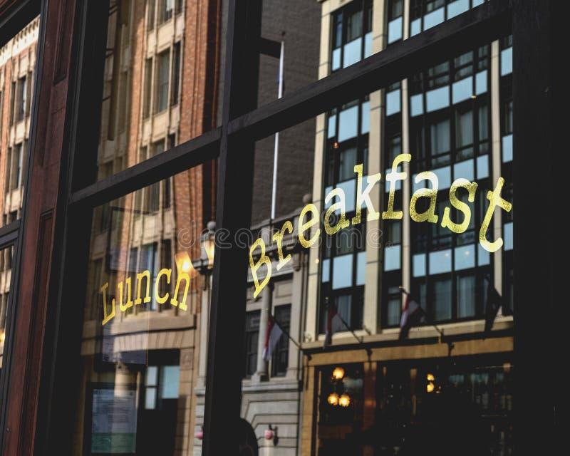 Café da manhã - Letras douradas na janela do restaurante com reflexo na cidade foto de stock