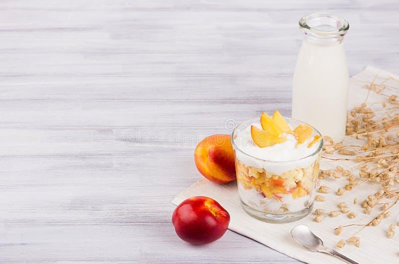 Café da manhã macio com flocos de milho, pêssego da fatia e garrafa de leite na placa de madeira branca fotos de stock royalty free
