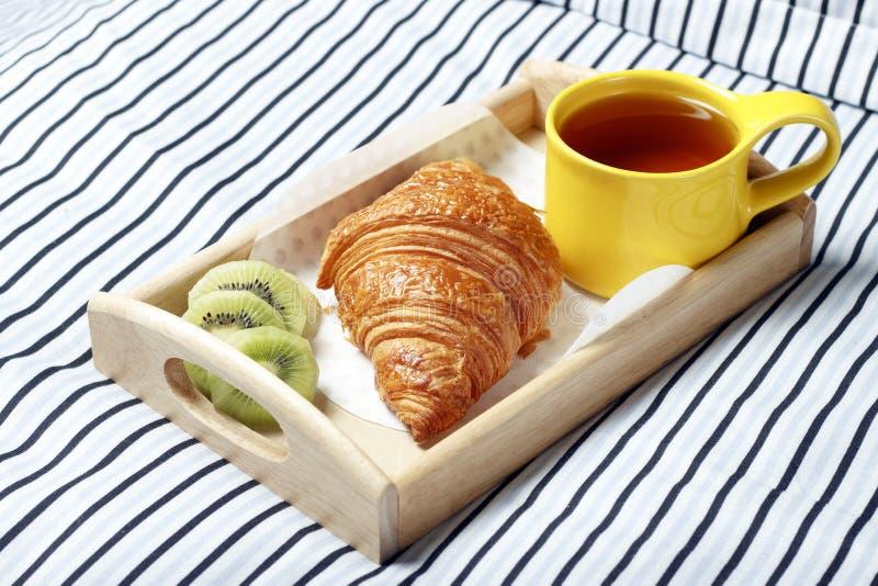 Café da manhã na cama, bandeja de madeira com chá, croissant e fruto imagens de stock royalty free