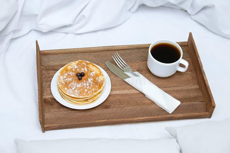 Café da manhã na cama em uma bandeja de madeira com panquecas do café imagens de stock royalty free