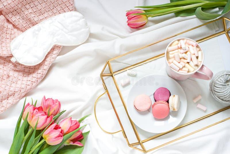 Café da manhã na composição colocada lisa pastel da cama com flores, um café do copo o e os doces foto de stock royalty free