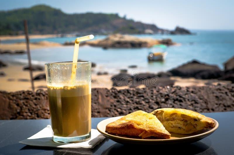 Café da manhã na praia Um sanduíche e um cocktail do café na tabela no restaurante no fundo do mar fotos de stock royalty free