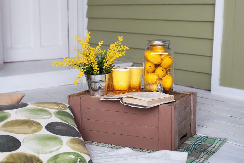 Café da manhã na varanda acolhedor Limonada caseiro no patamar em um dia quente Jarda do país do verão com descansos, flores da m imagem de stock