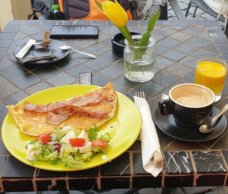 Café da manhã no quadrado da união de Timisoara Romênia com café e omellete e suco de laranja e salada fotografia de stock royalty free