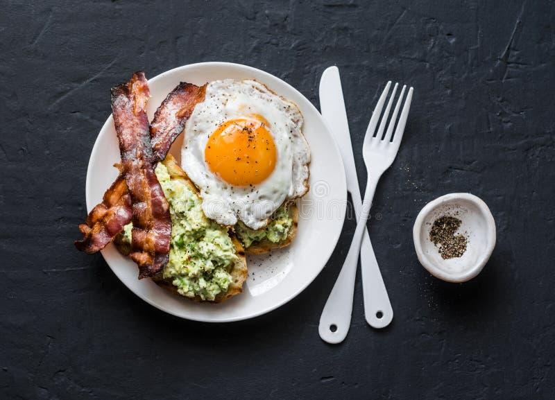 Café da manhã nutritivo saudável - brinde, bacon e ovo frito do abacate no fundo escuro imagem de stock