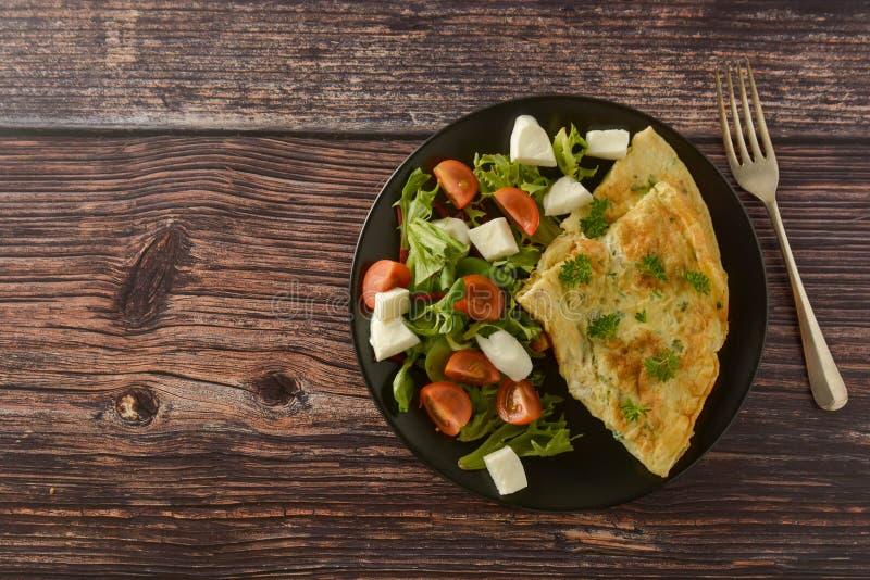 Café da manhã - omeleta do ovo com tomate, mussarela e verde de cereja Tabela de madeira com espa?o da c?pia imagem de stock royalty free