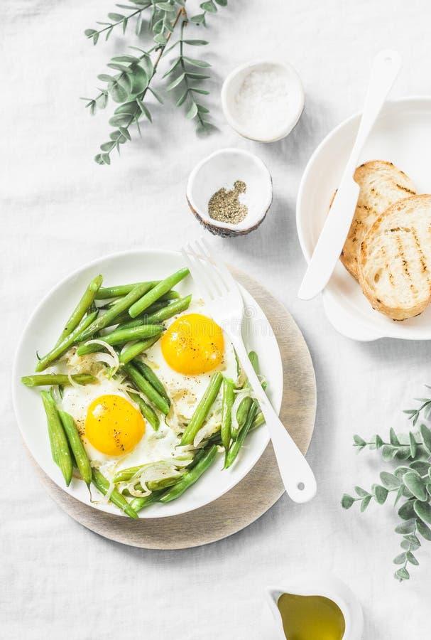 Café da manhã ou petisco saudável - um ovo frito com feijões verdes em um fundo claro fotos de stock