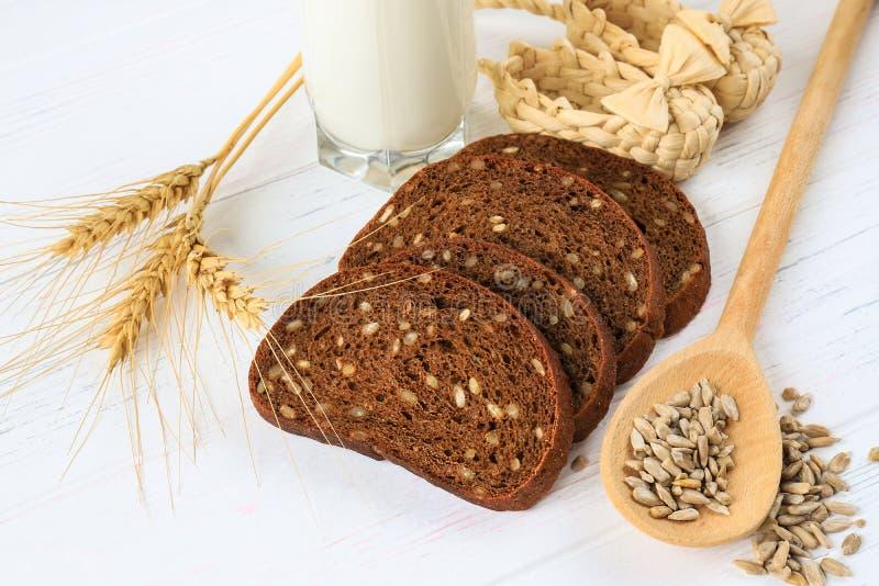 Café da manhã rústico em um fundo de madeira claro - pão, girassol, sementes em uma colher, trigo e um vidro do leite fotografia de stock
