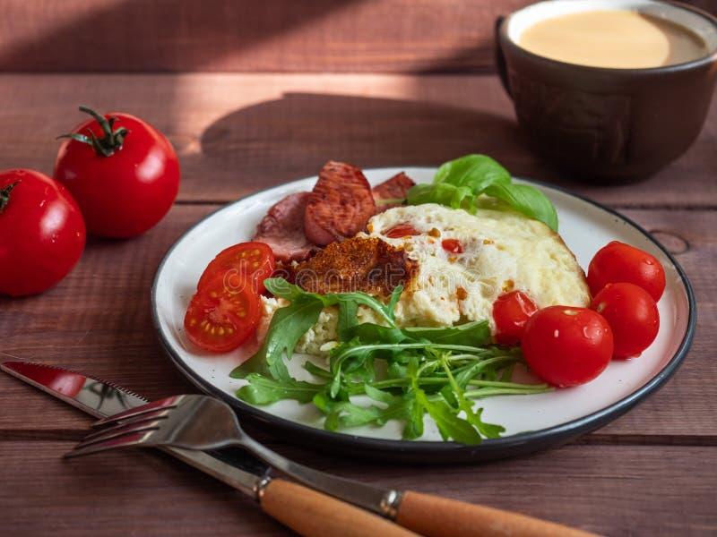 Café da manhã rico da omeleta com salsicha grelhada e tomates frescos e uma xícara de café com leite, cutelaria em uma bandeja de imagem de stock