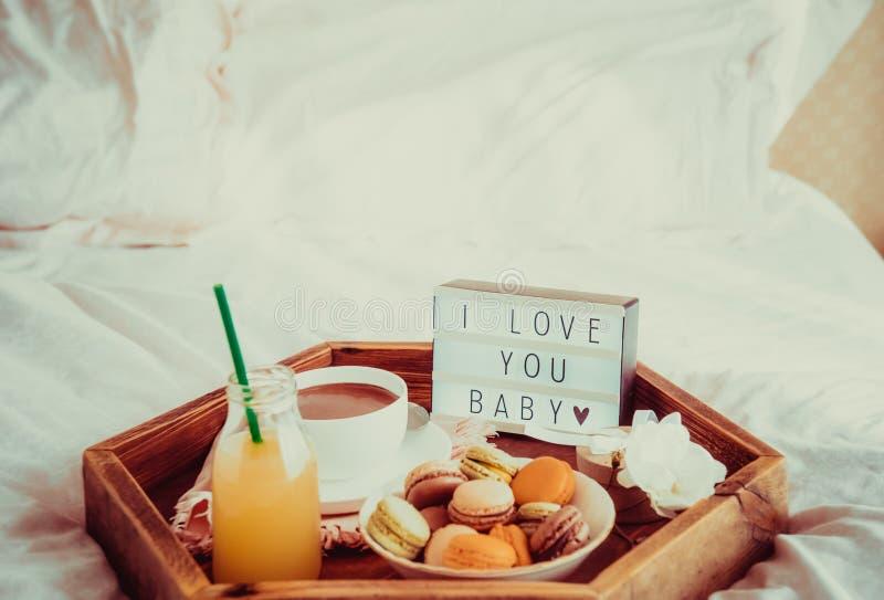 Café da manhã romântico na cama com eu te amo texto do bebê na caixa leve Xícara de café, suco, bolinhos de amêndoa, flor e caixa imagens de stock royalty free