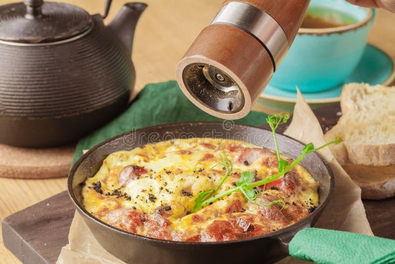 Café da manhã saboroso Shakshuka em uma bandeja do ferro Ovos fritos com tomates, cebola, salsa, pão e ervas Alimento saudável foto de stock royalty free