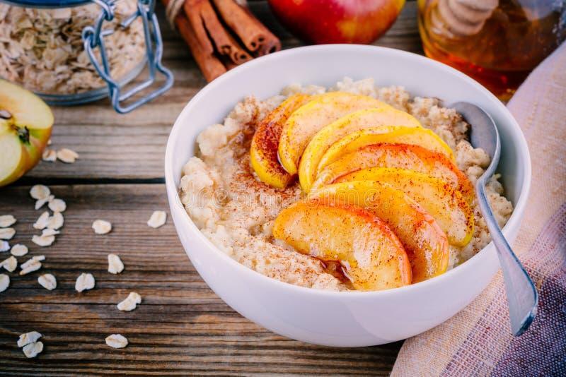 Café da manhã saudável: bacia da farinha de aveia com maçãs, canela e mel caramelizados foto de stock