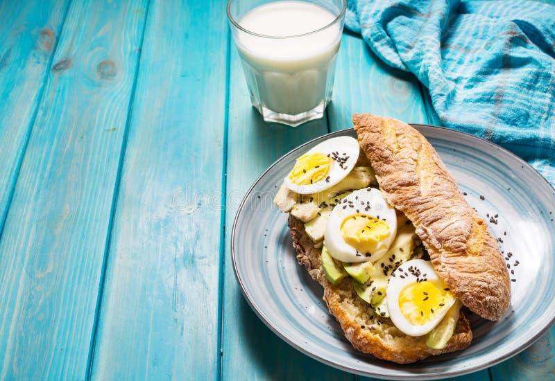 Café da manhã saudável - brinde com abacate, ovo e vidro do leite imagem de stock royalty free