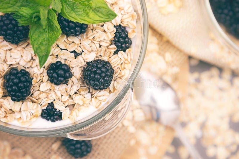 Café da manhã saudável com a bacia de musli e de amoras-pretas do cereal fotos de stock royalty free