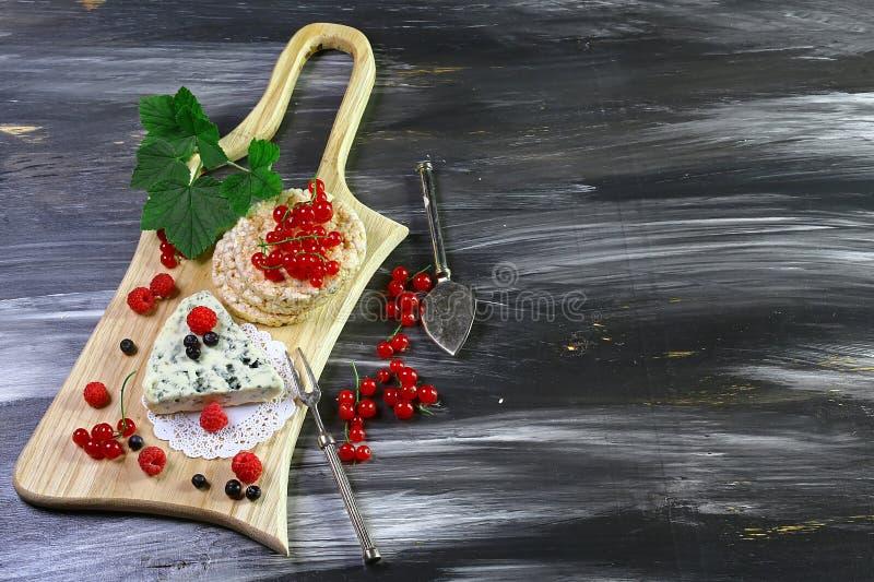 Café da manhã saudável com crispybread, molde no gosto do queijo do Bleu e bagas em uma placa de madeira Configuração lisa Copie  foto de stock