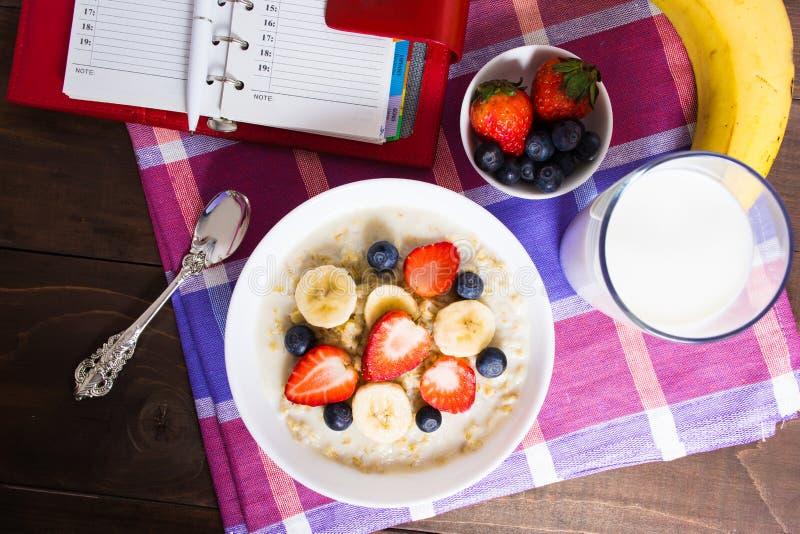 Café da manhã saudável com farinha de aveia, frutos e leite com planear o co imagens de stock
