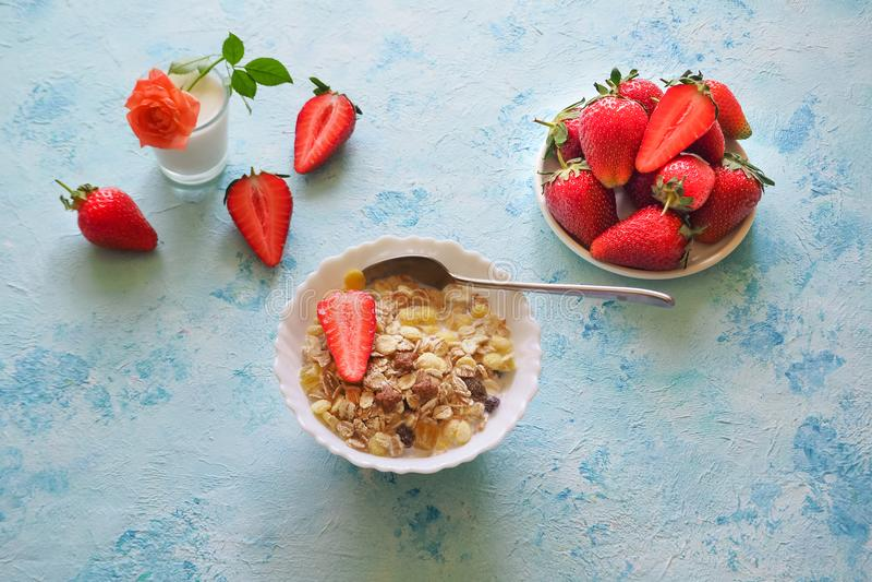 Café da manhã saudável com muesli, leite e morangos em um fundo azul fotografia de stock