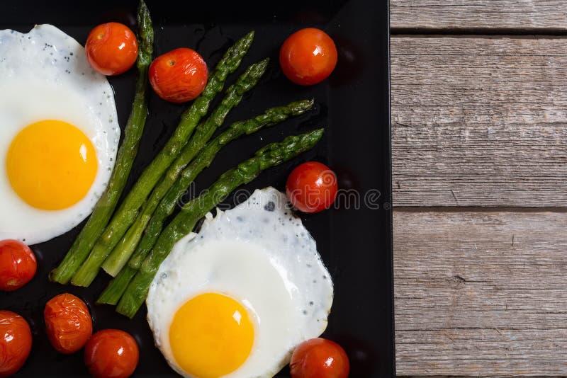 Café da manhã saudável com ovos, aspargo e tomates imagens de stock royalty free