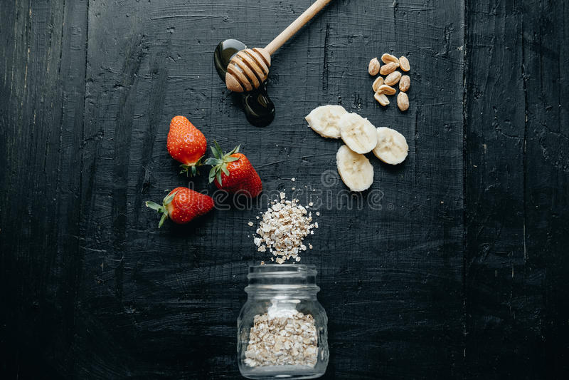 Café da manhã saudável da composição lisa da configuração: Farinha de aveia, morango, hon imagem de stock