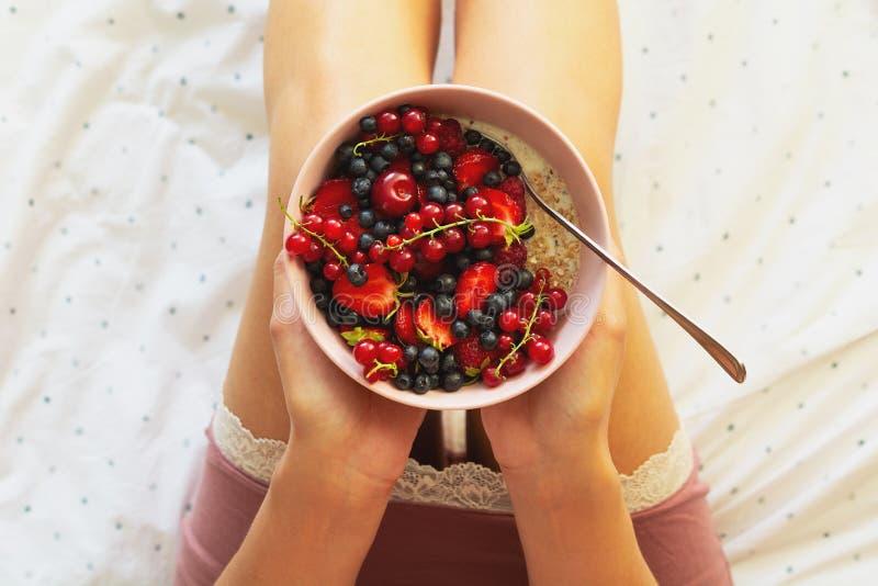 Café da manhã saudável do verão na cama Mulher que come o papa de aveia da farinha de aveia com bagas Conceito saud?vel comer Vis foto de stock royalty free