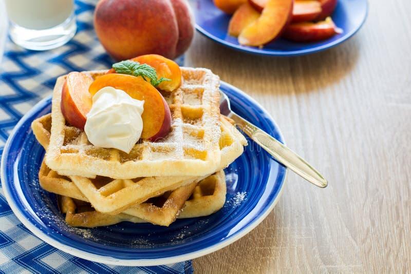 Café da manhã saudável: Os waffles belgas com fatias do pêssego e o creme decoraram as folhas de hortelã e o guardanapo azul foto de stock royalty free
