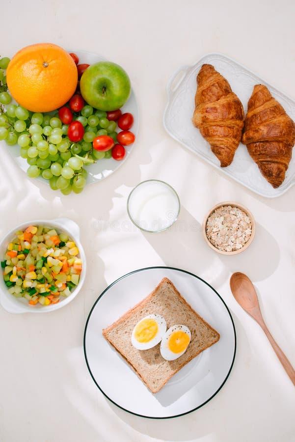 Café da manhã saudável servido com leite, croissant, ovo, cereais, farinha de aveia e frutos fotografia de stock royalty free