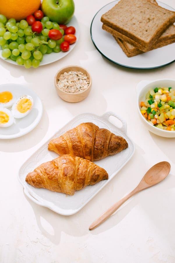 Café da manhã saudável servido com leite, croissant, ovo, cereais, farinha de aveia e frutos fotos de stock