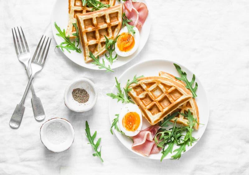 Café da manhã servido com os waffles saborosos, o ovo cozido, o presunto e a rúcula das batatas no fundo claro, vista superior Ap imagens de stock royalty free