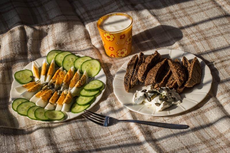 Café da manhã simples claro com ovos cozidos, iogurte e pepino fotos de stock