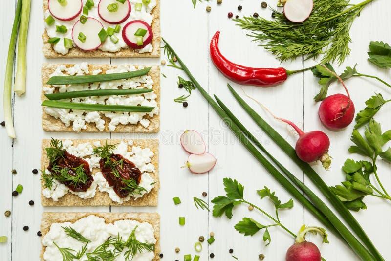 Café da manhã vegetal do vegetariano em um fundo de madeira branco Requeijão, rabanete, queijo, tomates sol-secados e verdes fotografia de stock royalty free