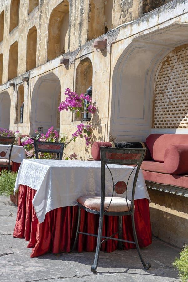 Café da rua na cidade velha, fora em Jaipur, Rajasthan, Índia Tabela, sofá e cadeiras perto da parede velha fotografia de stock royalty free