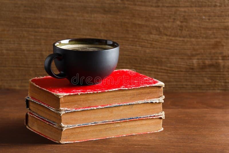 Café dans la tasse de forme de coeur de couleur rouge avec le vieux livre photographie stock
