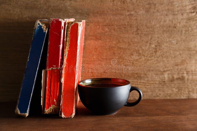 Café dans la tasse de forme de coeur de couleur rouge avec le vieux livre image stock