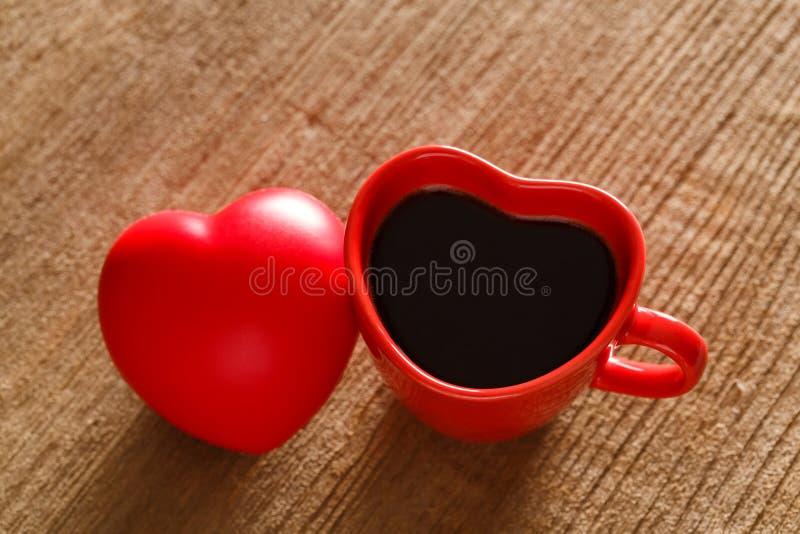 Café dans la tasse de forme de coeur de couleur rouge sur la table en bois photo libre de droits