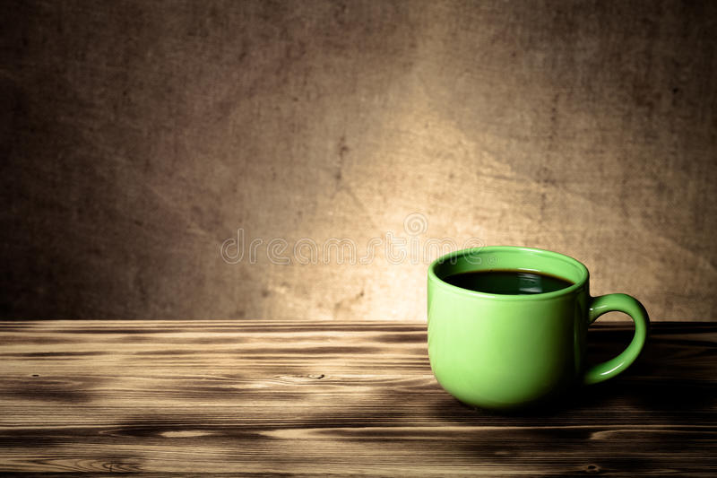 Café dans la tasse sur la table en bois vis-à-vis d'un backgr defocused de toile de jute photo stock