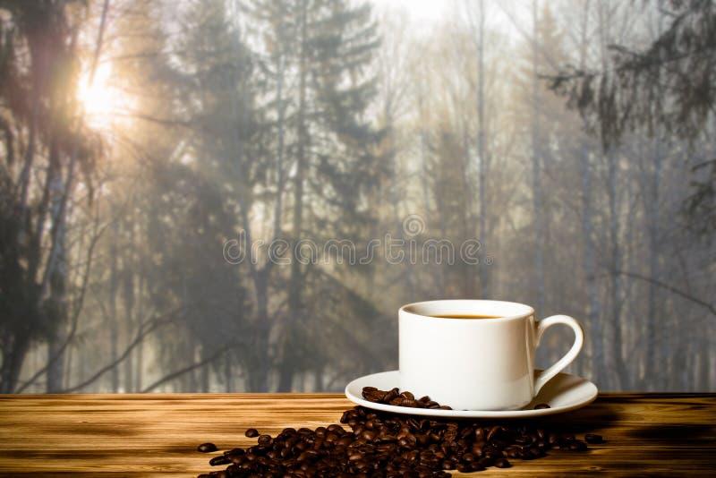 Café dans la tasse sur la table en bois vis-à-vis du fond brouillé Colla image stock