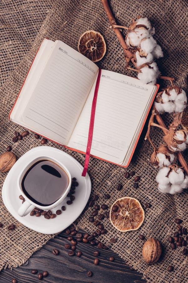 Café dans une tasse avec une vue supérieure de style plat de bloc-notes et de coton photo libre de droits
