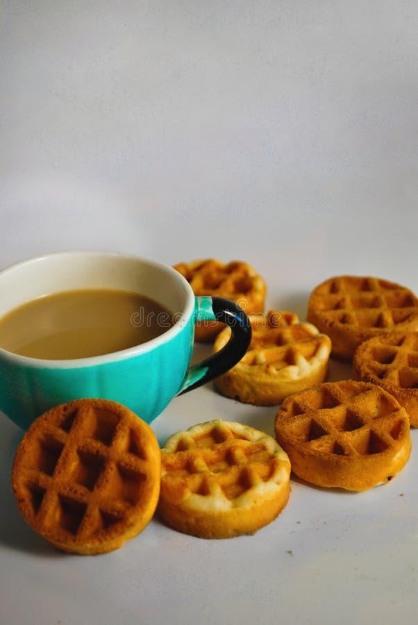 Café dans une tasse bleue et des gaufres molles rondes illustration libre de droits