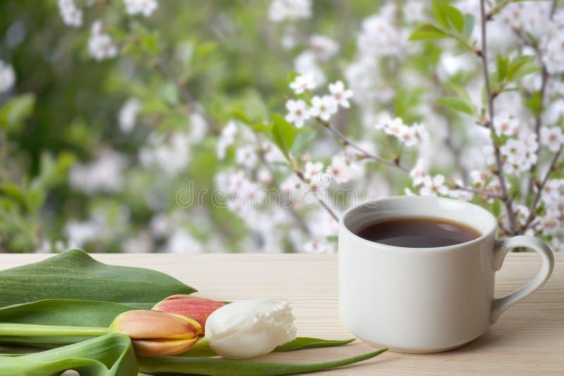 Café dans une tasse et des tulipes sur la table en bois vis-à-vis d'un defocused image stock