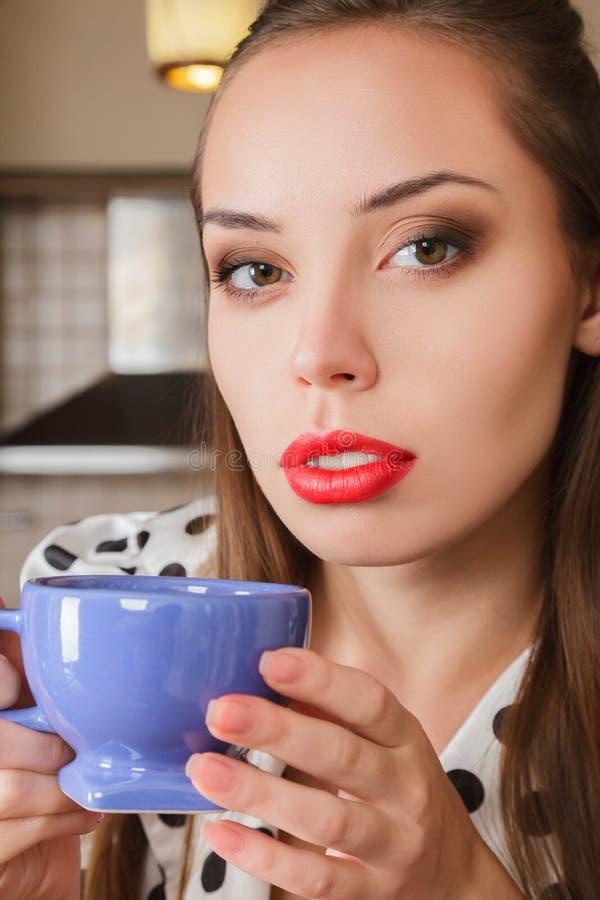 Café de boissons de jeune femme à la maison images libres de droits