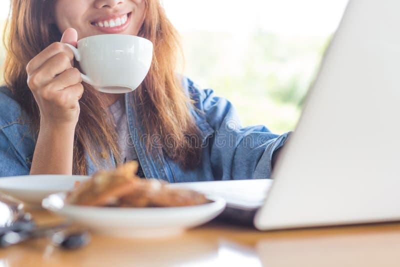 Café de boissons de sourire de femmes et ordinateur d'utilisation photo libre de droits