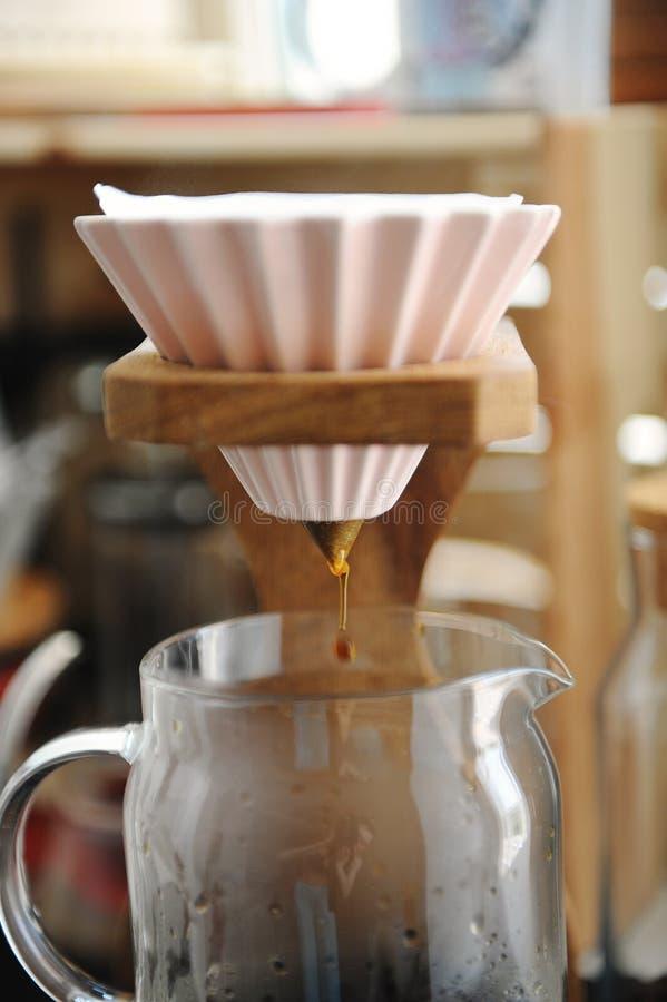 Café de brassage dans le dispositif d'écoulement en céramique rose d'origami sur le support en bois Le manuel alternatif brassent images stock