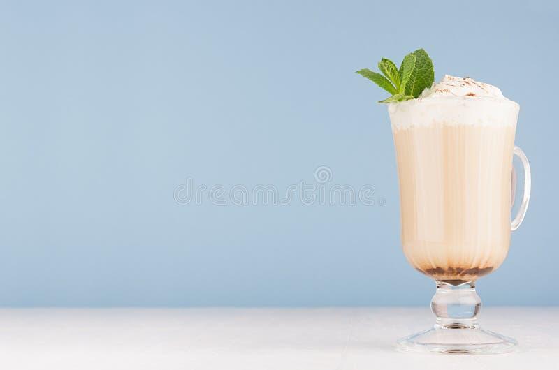 Café de cappuccino avec la crème fouettée, menthe verte, poudre de cacao en verre transparent avec des poignées sur le mur bleu e photographie stock libre de droits