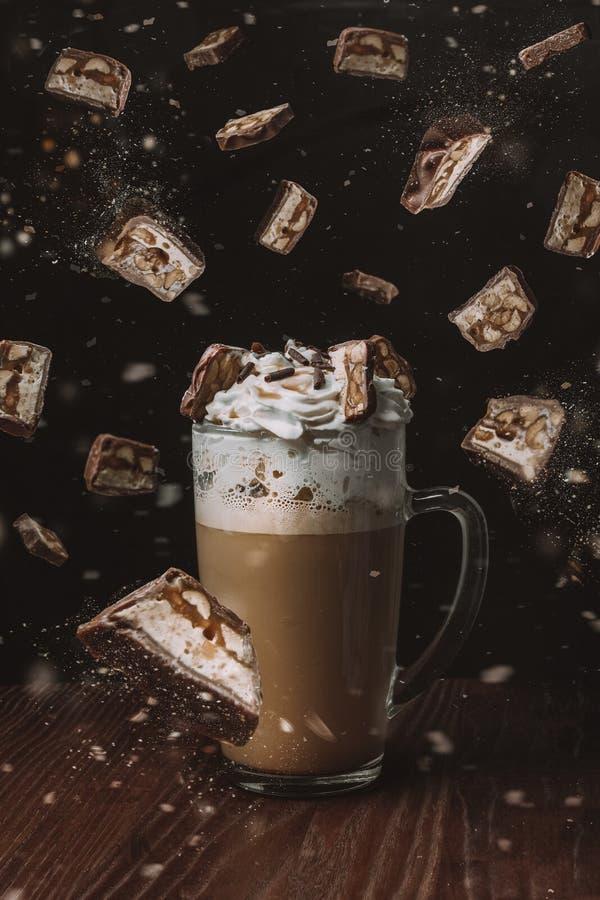 café de cappuccino avec un chapeau de crème fouettée, garni avec des morceaux de chocolat image libre de droits