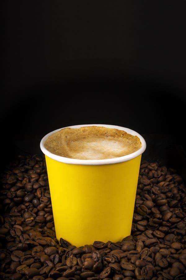 Caf? de cappuccino dans la tasse de papier sur les grains de caf? naturels sur l'obscurit? photographie stock
