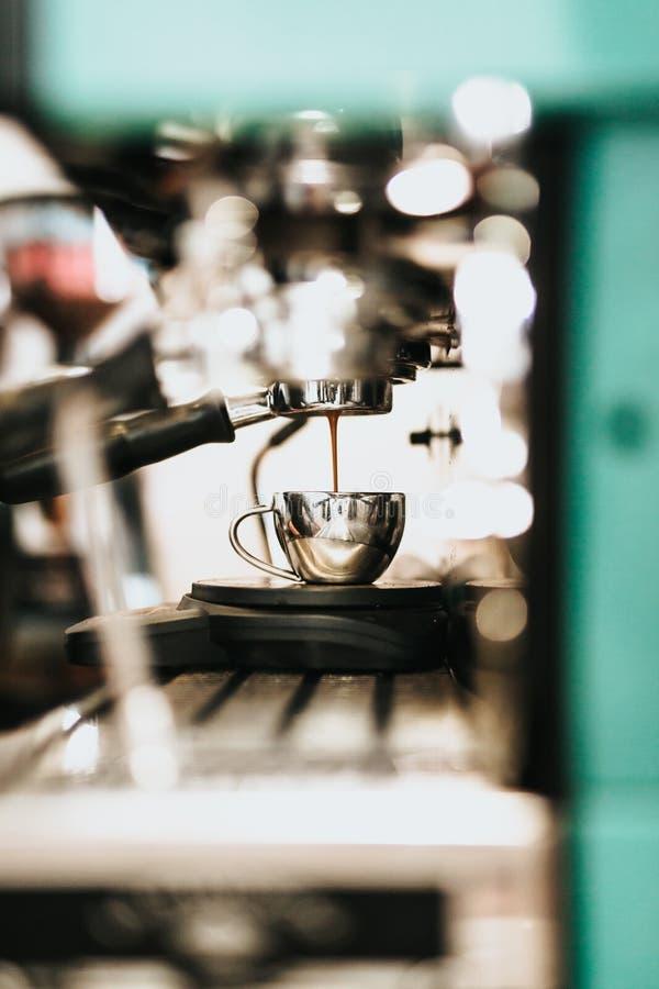 Café de colada de café del metal de la máquina grande del fabricante en una taza del metal imagen de archivo libre de regalías