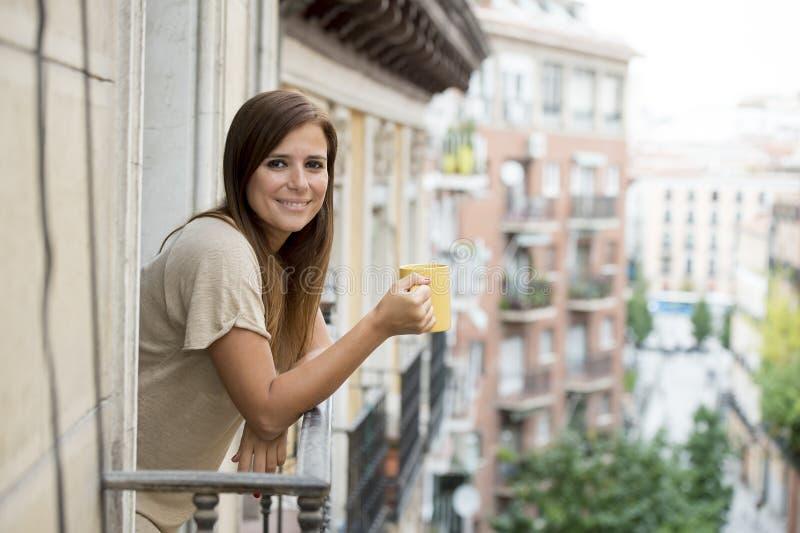 Café de consumición alegre relajado del té de la mujer hermosa en la terraza del balcón del apartamento imagen de archivo