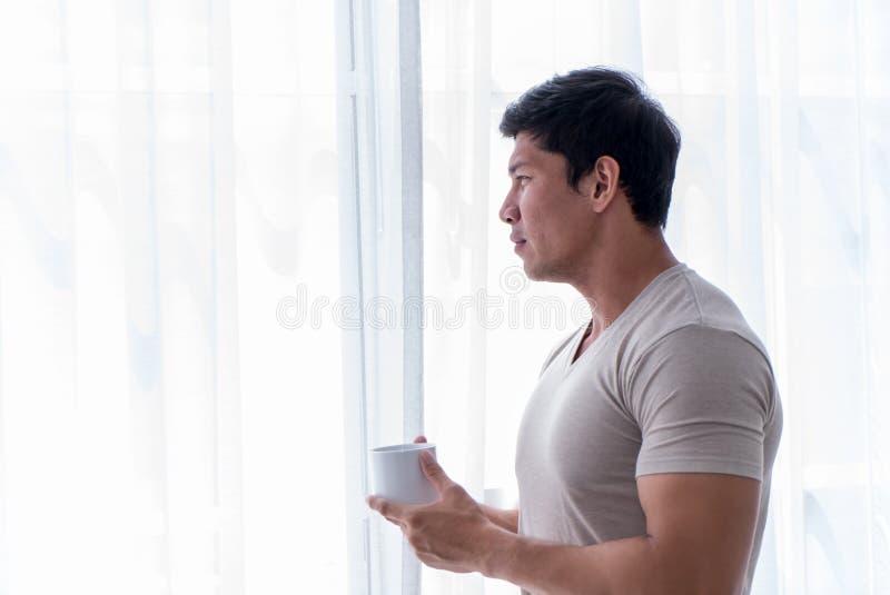 Café de consumición asiático del té del hombre fuerte por las ventanas de la mañana fotografía de archivo