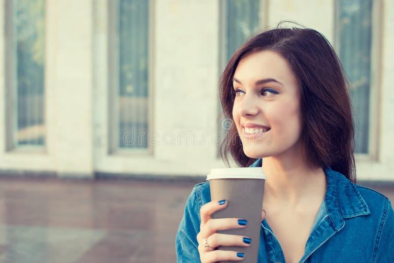 Café de consumición de la mujer al aire libre que sostiene la taza de papel imagen de archivo libre de regalías